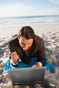 Happy businessman lying on a beach towel Stock Photos