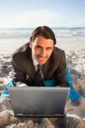 Young smiling businessman lying on a beach towel - stock photo
