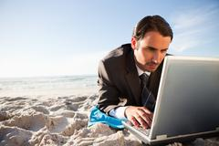 Young businessman looking at his laptop on the beach - stock photo