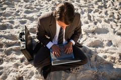 Overhead view of a young businessman sitting cross-legged on the beach Stock Photos