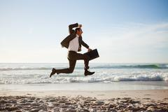 Young businessman jumping on the beach with his briefcase Stock Photos