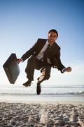 Successful businessman showing his happiness by jumping on the beach - stock photo