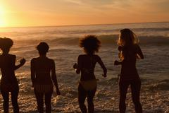 Four young women standing upright on the beach - stock photo
