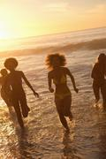 Four young women running in the water at sunset - stock photo