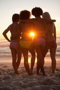 Rear view of young friends holding each other in front of the sunset - stock photo