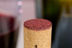 Red wine soaked cork in front of glass Stock Photos