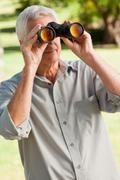 Old man looking through a binoculars Stock Photos
