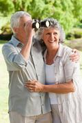 A man is looking through a binoculars and hugs his smiling wife Stock Photos