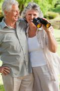 Woman holds a binoculars and husbands hugs her Stock Photos