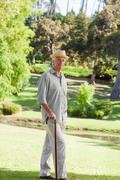 Old man with walking stick outdoors in the sunshine - stock photo