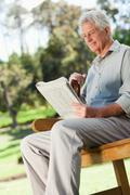 Old man sitting down smiling and holding a newspaper - stock photo
