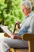 Old man sitting down reading a newspaper Stock Photos