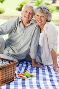 Smiling couple looking at the camera having a picnic Stock Photos
