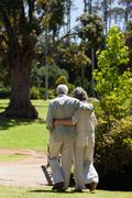 Elderly couple with their arms around each other walking in the park Stock Photos