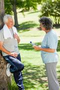 Man in running gear is leaning against a tree talking to a woman Stock Photos