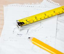 carpenter pencil and rule on plans - stock photo