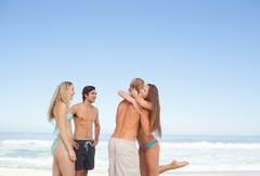 Stock Photo of Two friends hugging on a seaside while their friends watch