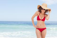 Woman in beachwear smiling while holding the brim of her hat - stock photo