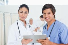 Stock Photo of Intern smiling while holding a clipboard with a serious doctor