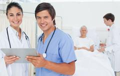Stock Photo of Doctor and an intern smiling as they hold a clipboard