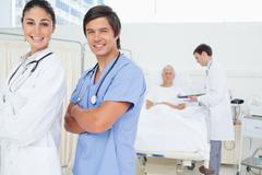Doctor and an intern looking to their side while smiling and crossing their arms - stock photo