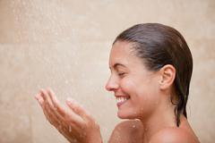 Side view of smiling woman enjoying a shower Stock Photos