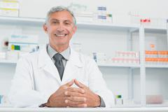 Happy male pharmacist with his hands joined on a counter Stock Photos