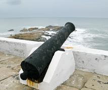 elmina castle rusty gun overlooking ocean - stock photo