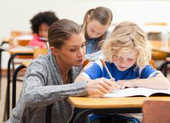 Helpful teacher next to a student Stock Photos