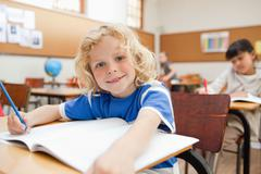 Smiling boy sitting at desk with exercise book - stock photo