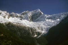 Steep ridged mountain with glacier icefall Stock Photos