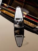 Metronome ticking and reflected on piano Stock Photos