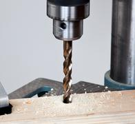 close up of drill bit above wood - stock photo