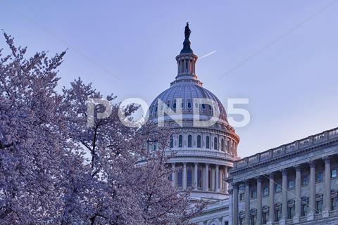 Stock photo of sunrise behind the dome of the capitol in dc