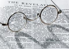 antique reading glasses on page of bible - stock photo