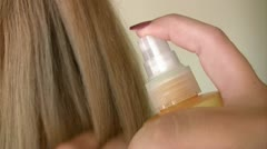 Woman applying hair lotion Stock Footage