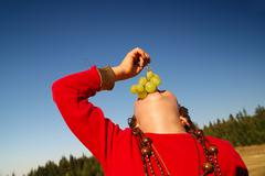 Stock Photo of happy girl with grape outside