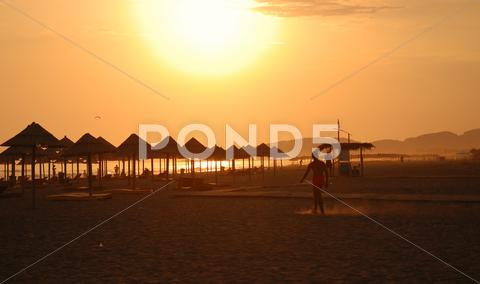 Stock photo of sunshine on beach with beach umbrellas silhouette