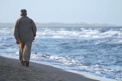 lonely older  man walking on beach - stock photo