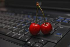 fresh cherry on laptop keyboard - stock photo