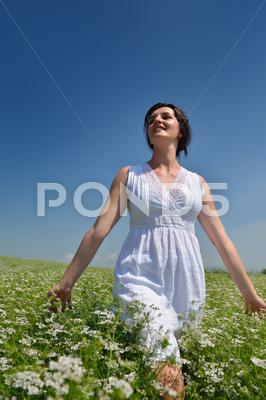 Stock photo of young happy woman in green field