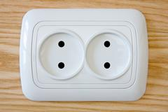 white electric outlet on wooden wall - stock photo