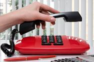 Stock Photo of hand picking up the handset of telephone