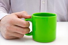 Stock Photo of businessman hold a green cup