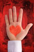 Stock Photo of hand with heart shape on dark red background