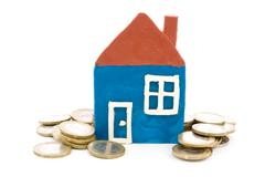 house and coins over a white background - stock photo
