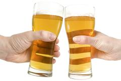Two hands holding beers making a toast Stock Photos