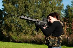 Beautiful girl with a gun Stock Photos