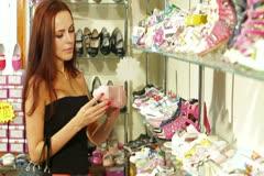 Stock Video Footage of Woman Choosing Footwear in Children's Shoe Store