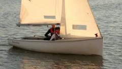 two men in a dinghy sail in warm evening light - stock footage